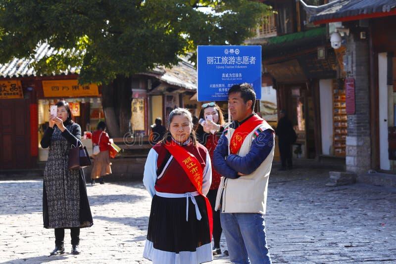 Voluntários do turismo em um quadrado na cidade velha de Lijiang, Yunnan, China imagens de stock