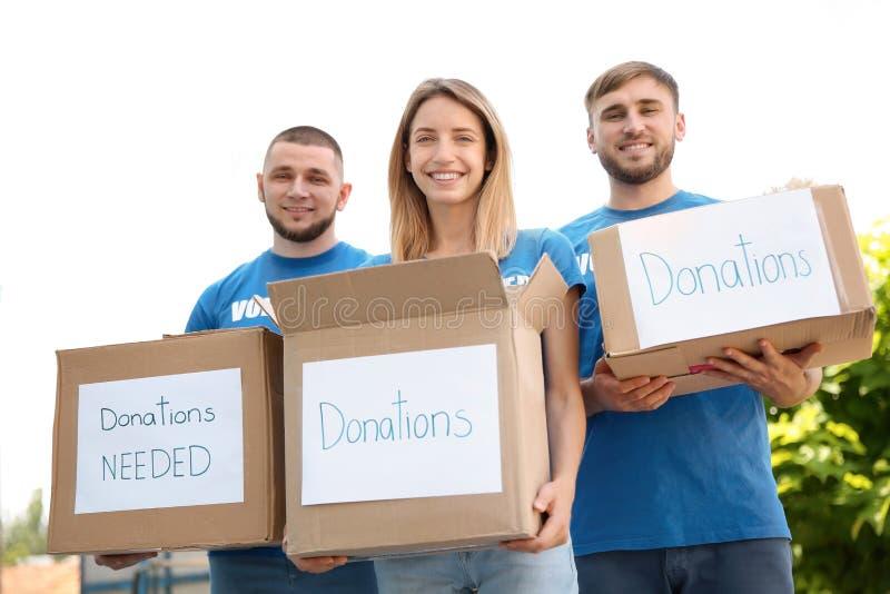 Voluntários dos jovens que guardam caixas com doações fotografia de stock royalty free