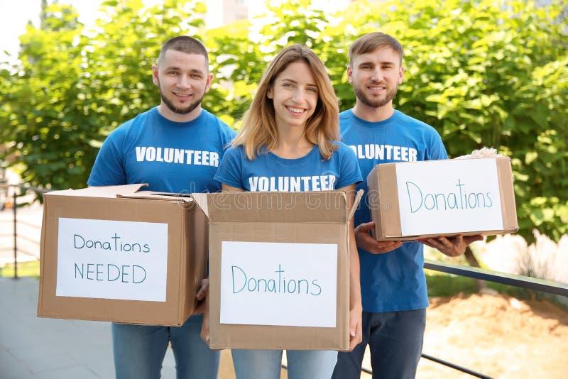 Voluntários dos jovens que guardam caixas com doações imagem de stock royalty free