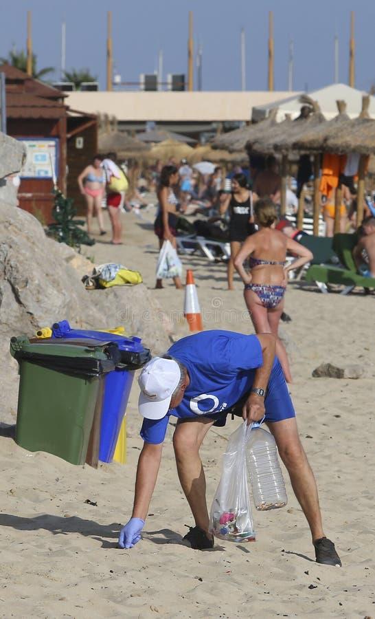 Voluntários durante a limpeza ambiental na praia no detalhe de mallorca imagem de stock