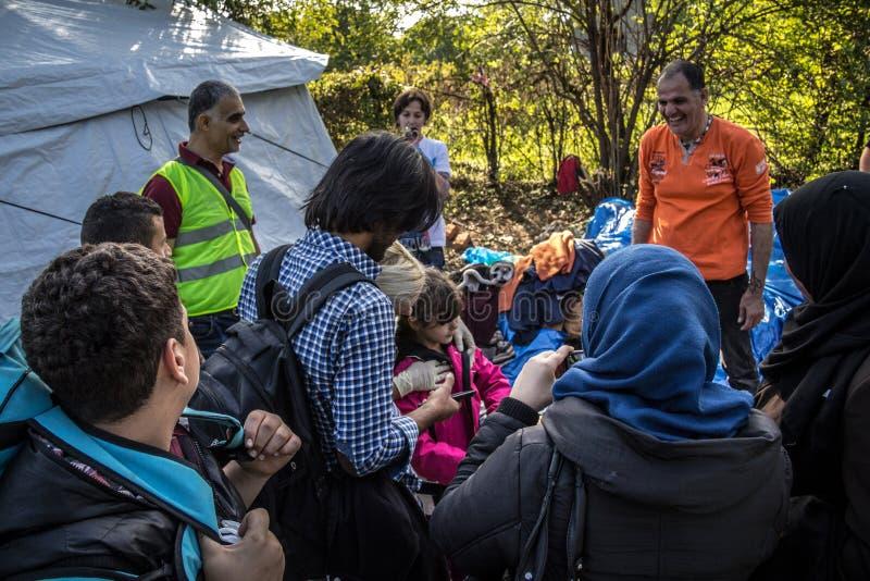 Voluntários e refugiados que olham doações da roupa na beira da Sérvia da Croácia, entre as cidades de Bapska & Berkasovo imagens de stock