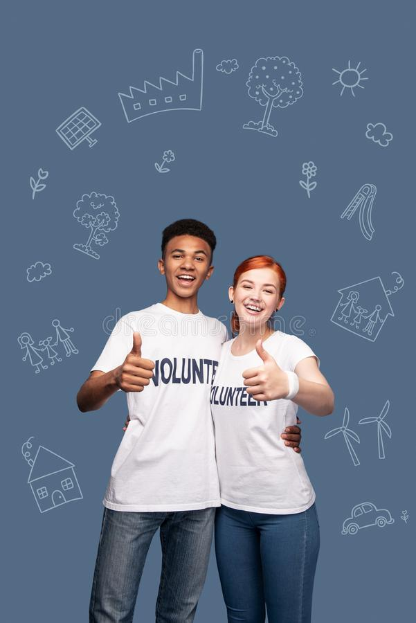 Voluntários emocionais que sorriem e que colocam seus polegares foto de stock royalty free