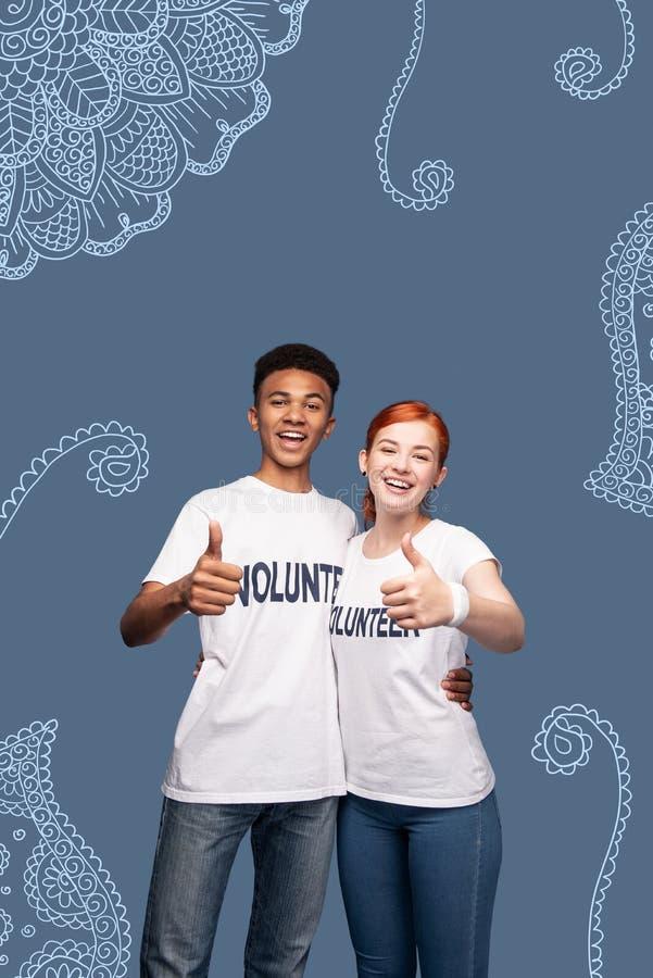 Voluntários entusiasmado que abraçam e que colocam seus polegares fotos de stock