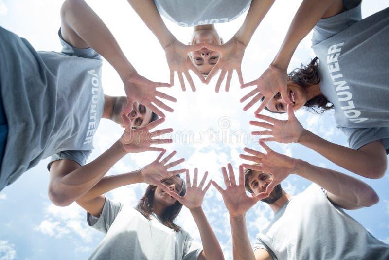 Voluntários felizes que jogam com suas mãos foto de stock