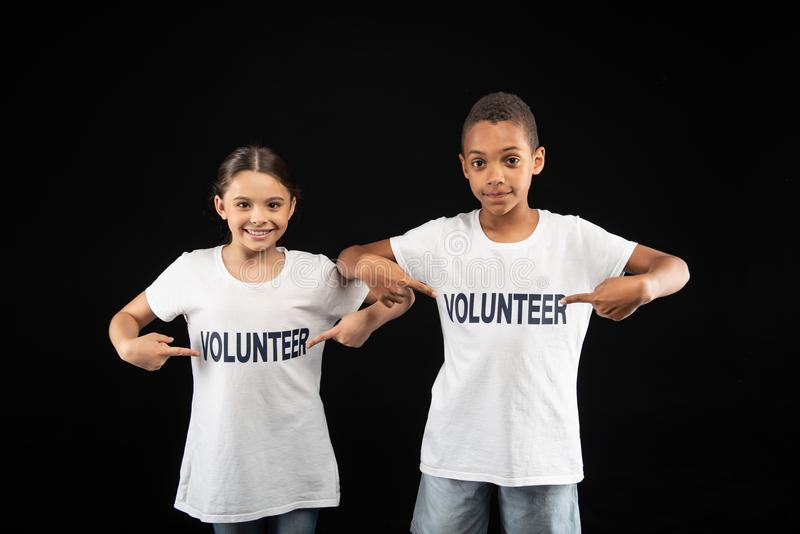 Voluntários inspirados dos jovens que vestem as camisas brancas foto de stock