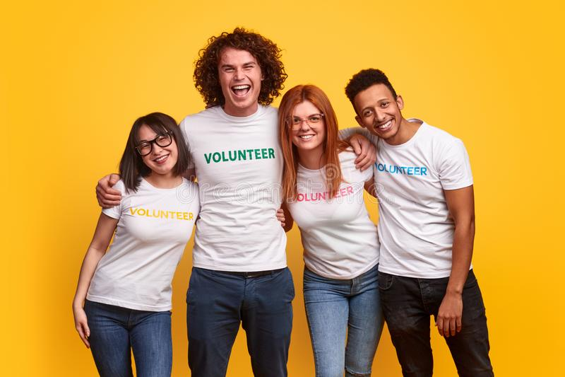 Voluntários multi-étnicos felizes que abraçam-se imagens de stock