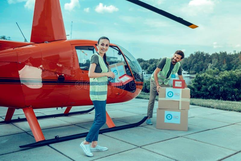 Voluntários novos ativos nos revestimentos verdes que colocam caixas para dentro do helicóptero imagens de stock royalty free