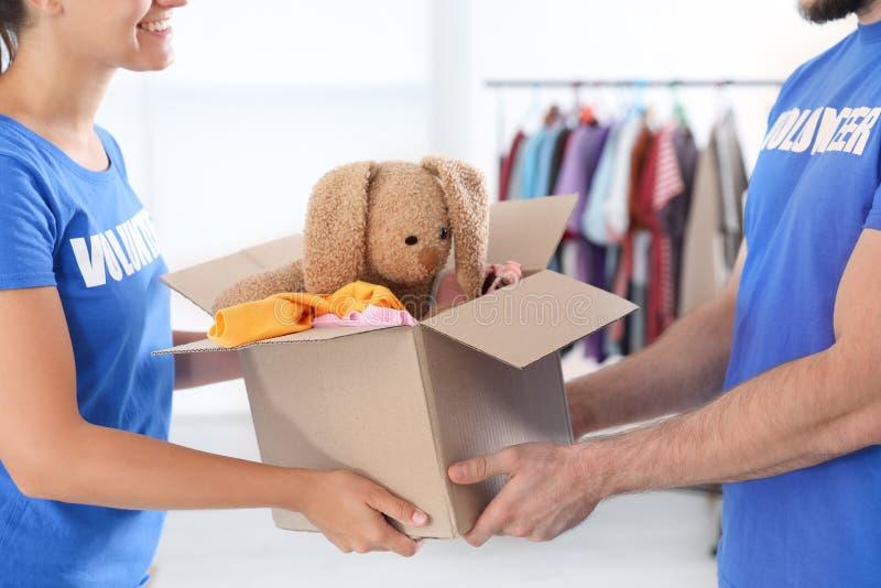 Voluntários novos que guardam a caixa com doações dentro fotos de stock royalty free