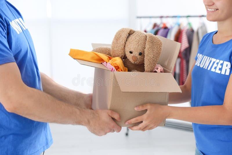 Voluntários novos que guardam a caixa com doações dentro foto de stock