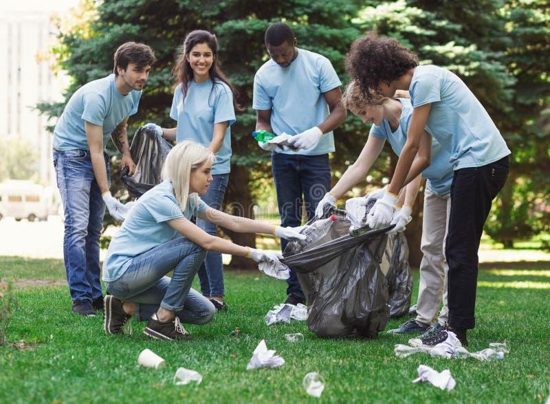 Voluntários novos que recolhem o lixo no parque do suumer imagens de stock royalty free