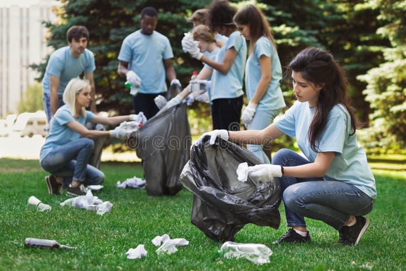 Voluntários novos que recolhem o lixo no parque do suumer foto de stock royalty free
