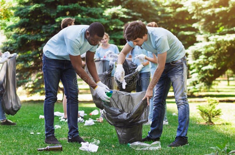 Voluntários otimistas que guardam o saco de lixo no parque foto de stock royalty free