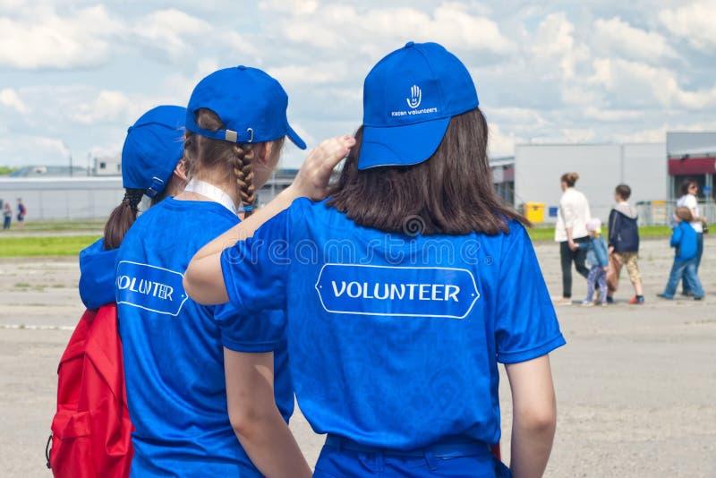 Voluntários que cumprimentam povos no evento de esportes imagens de stock royalty free