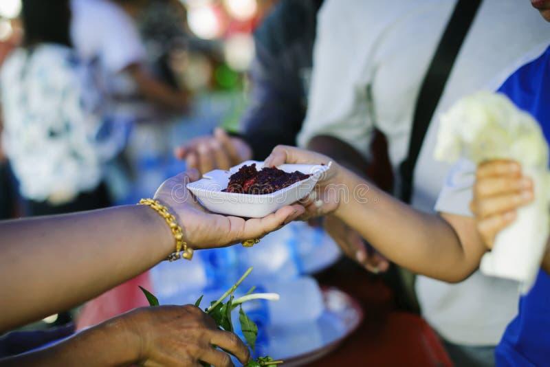 Voluntários que dão o alimento aos povos pobres na necessidade desesperada: O conceito do alimento que compartilha para ajudar a  imagem de stock