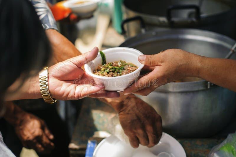 Voluntários que dão o alimento aos povos pobres na necessidade desesperada: O conceito do alimento que compartilha para ajudar a  fotografia de stock