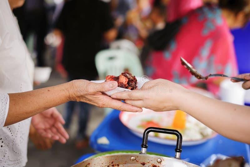 Voluntários que dão o alimento aos povos pobres na necessidade desesperada: O conceito do alimento que compartilha para ajudar a  imagem de stock royalty free