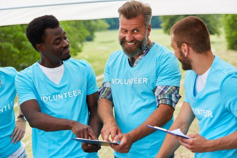 Voluntários que discutem uma ação de relevo imagens de stock