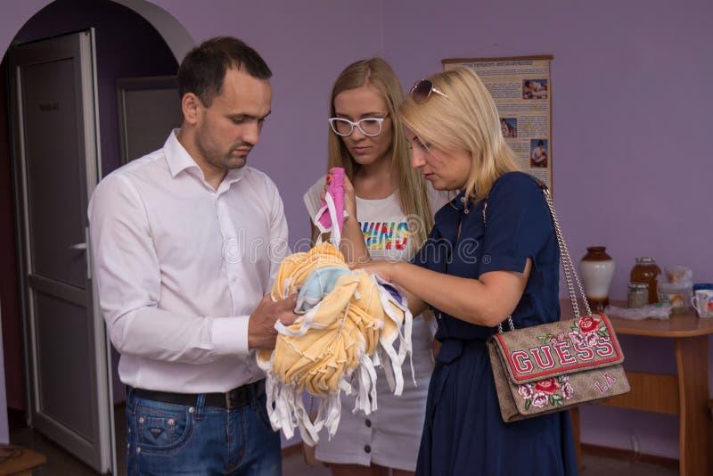 Voluntários que doam a roupa para bebês no hospital de maternidade durante o dia da proteção das crianças imagem de stock royalty free