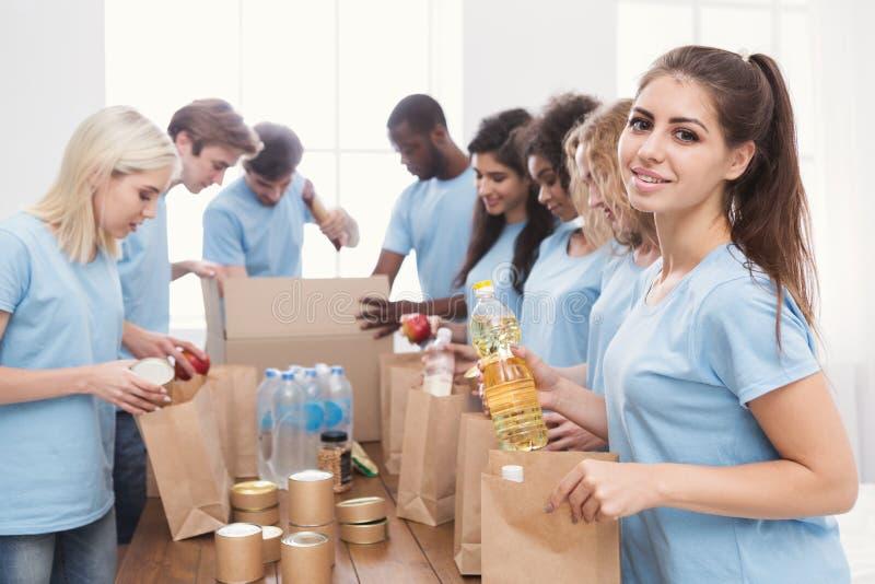 Voluntários que embalam o alimento e as bebidas em sacos de papel imagem de stock royalty free