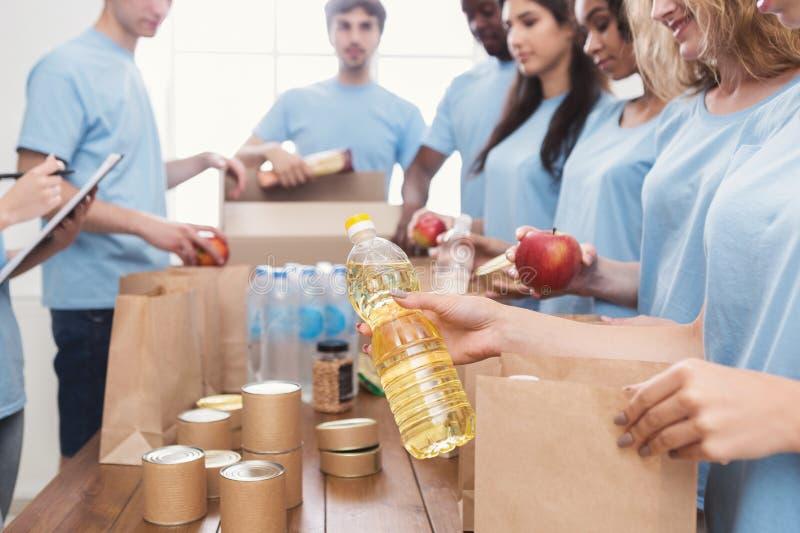 Voluntários que embalam o alimento e as bebidas em sacos de papel fotografia de stock royalty free