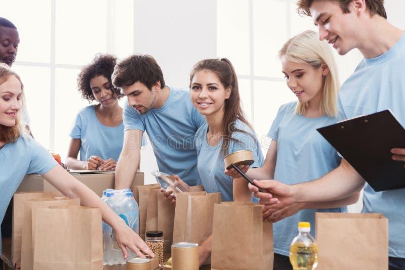 Voluntários que embalam o alimento e as bebidas em sacos de papel foto de stock