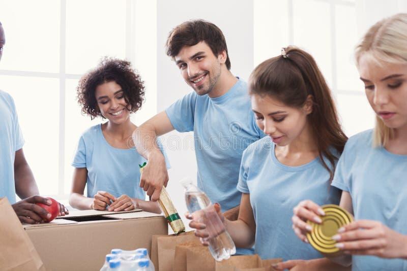 Voluntários que embalam o alimento e as bebidas em sacos de papel imagem de stock