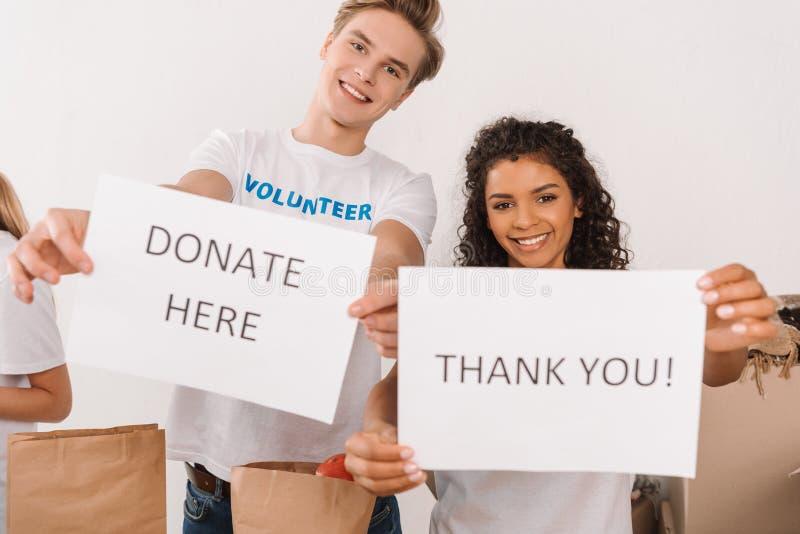 Voluntários que guardam cartazes da caridade imagem de stock royalty free