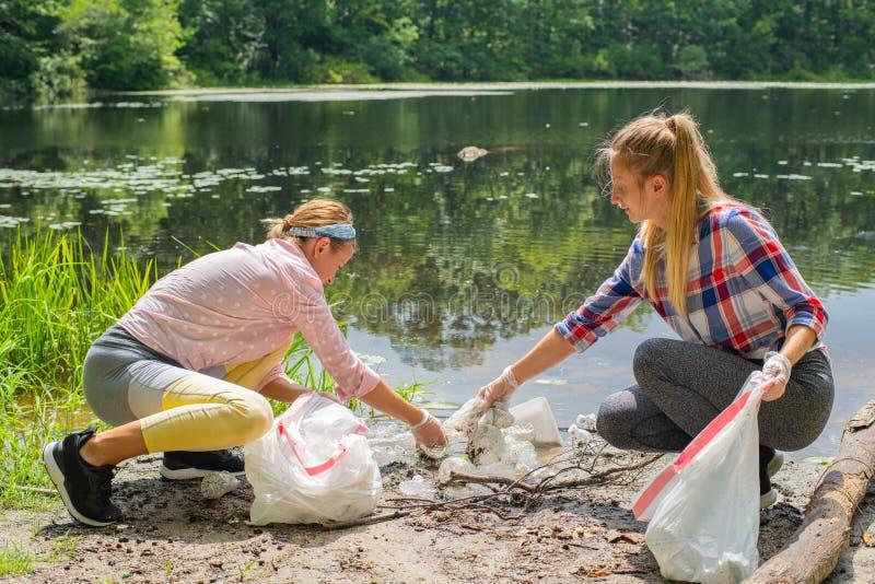 Voluntários que limpam o lixo perto do rio Mulheres que pegaram um plástico da garrafa no lago, na poluição e no ambiente fotos de stock royalty free