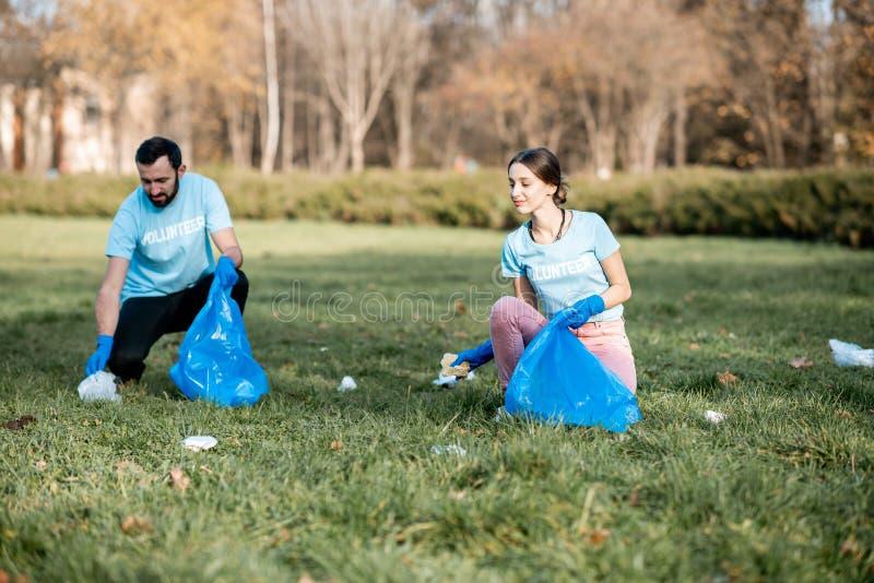 Voluntários que limpam o parque público dos desperdícios foto de stock