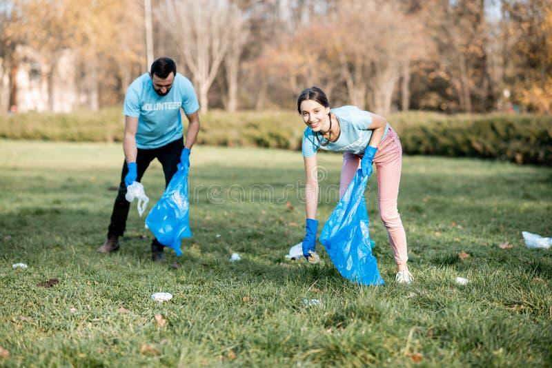 Voluntários que limpam o parque público dos desperdícios fotografia de stock