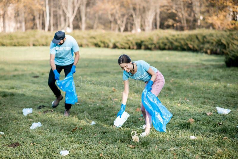 Voluntários que limpam o parque público dos desperdícios fotografia de stock royalty free