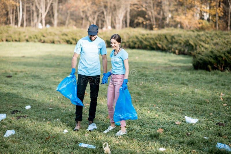 Voluntários que limpam o parque público dos desperdícios fotos de stock