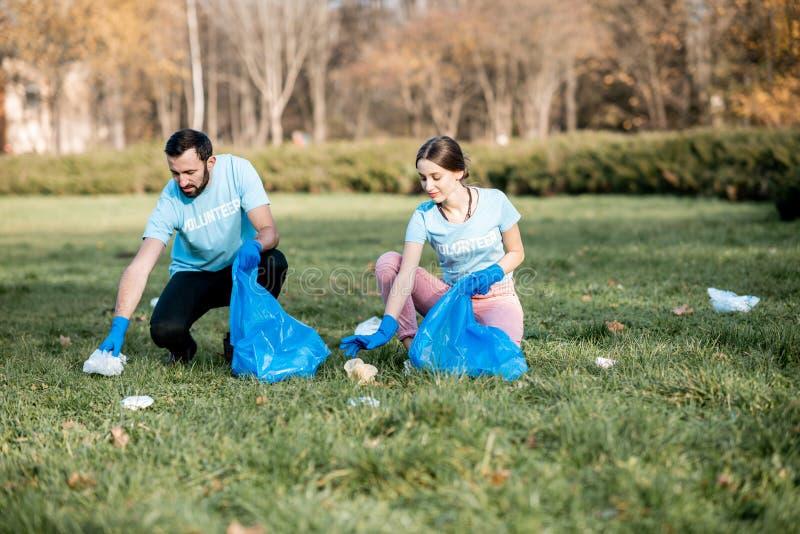 Voluntários que limpam o parque público dos desperdícios imagens de stock royalty free