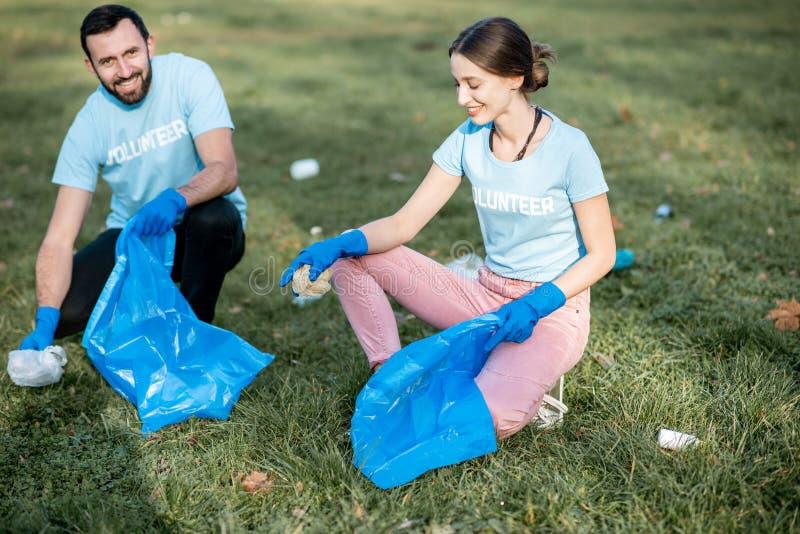 Voluntários que limpam o parque público dos desperdícios imagem de stock