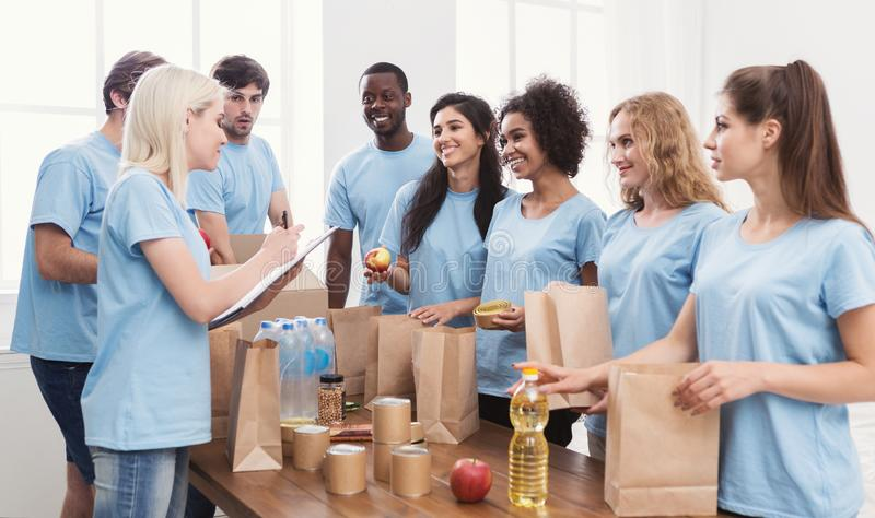 Voluntários que põem o alimento e as bebidas em sacos de papel fotografia de stock
