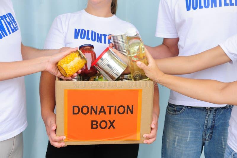 Voluntários que põr o alimento na caixa da doação fotografia de stock