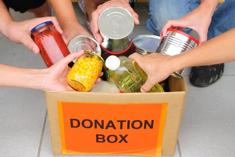 Voluntários que põr o alimento na caixa da doação fotografia de stock royalty free