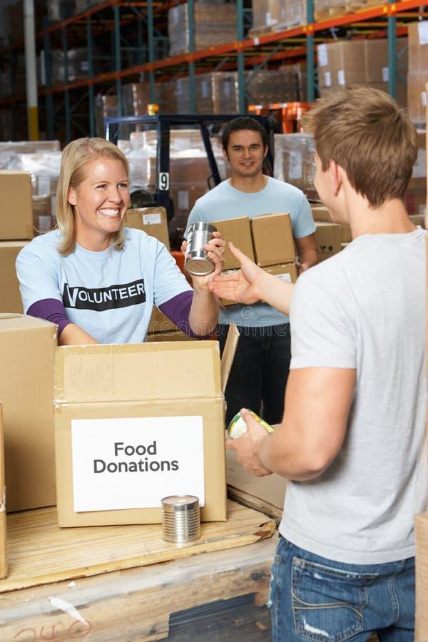 Voluntários que recolhem doações do alimento no armazém foto de stock