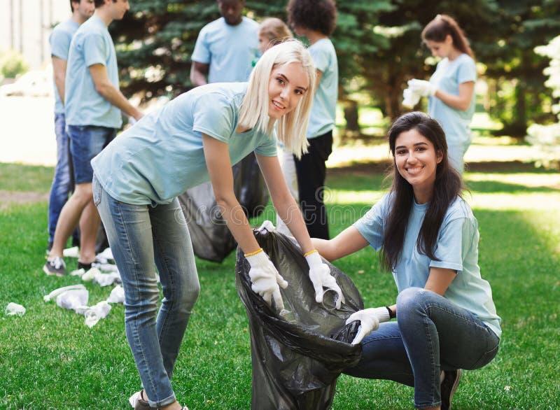 Voluntários que recolhem garrafas plásticas recicláveis no parque imagem de stock