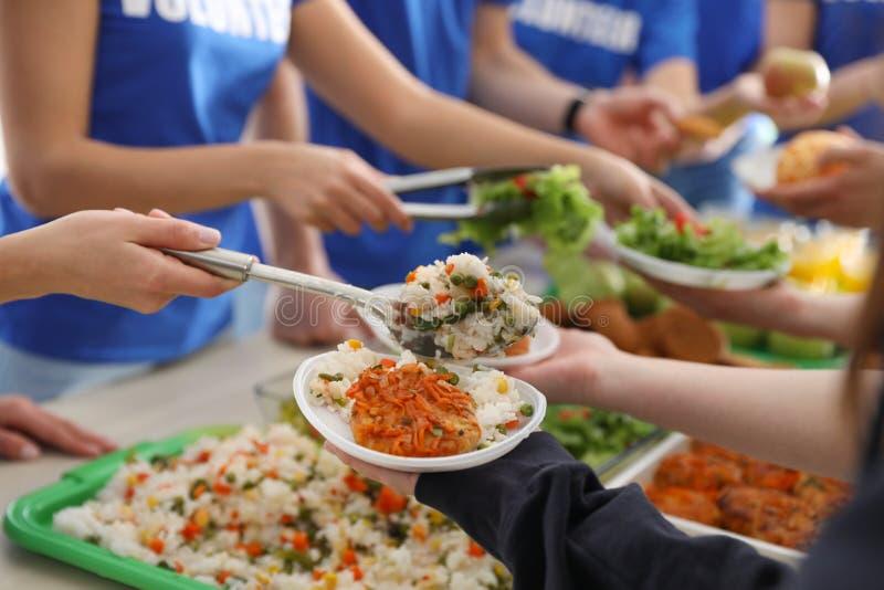 Voluntários que servem o alimento aos povos pobres, fotos de stock