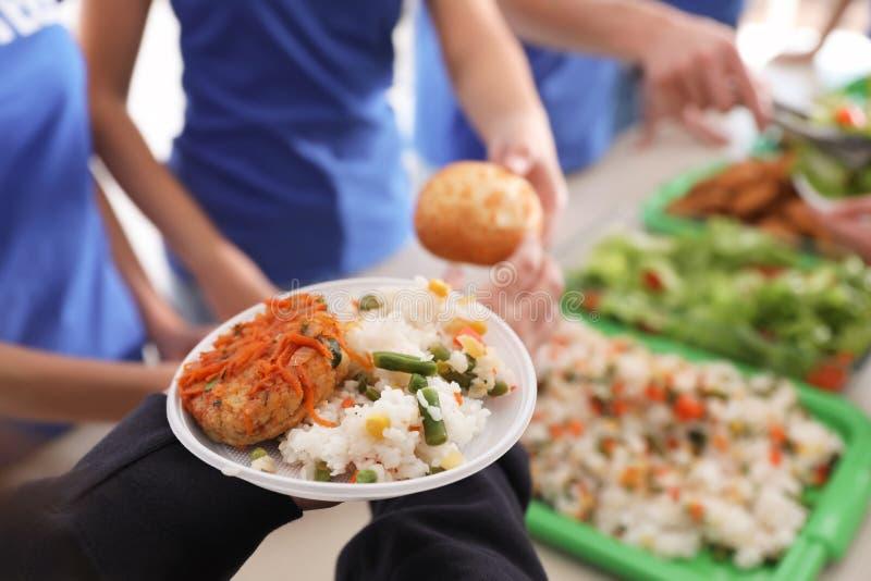 Voluntários que servem o alimento aos povos pobres imagens de stock royalty free