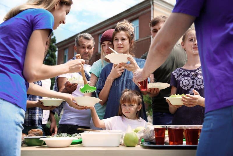 Voluntários que servem o alimento para povos pobres fotos de stock
