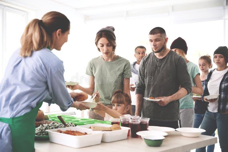 Voluntários que servem o alimento para povos pobres imagem de stock