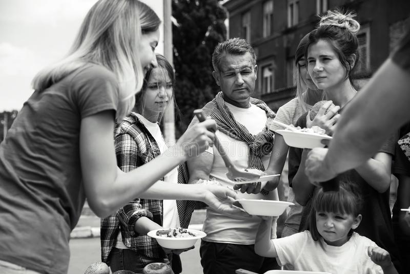 Voluntários que servem o alimento para povos pobres fora imagens de stock