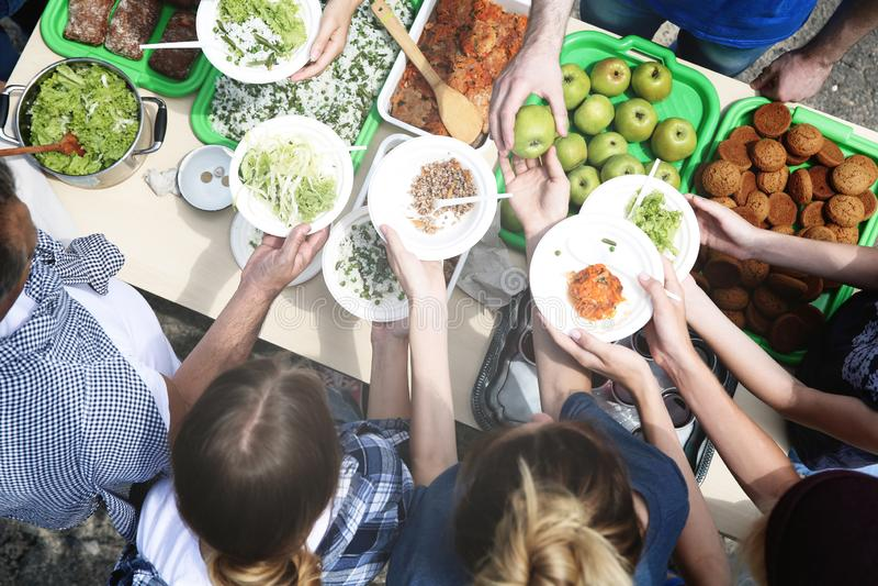 Voluntários que servem o alimento para povos pobres foto de stock royalty free