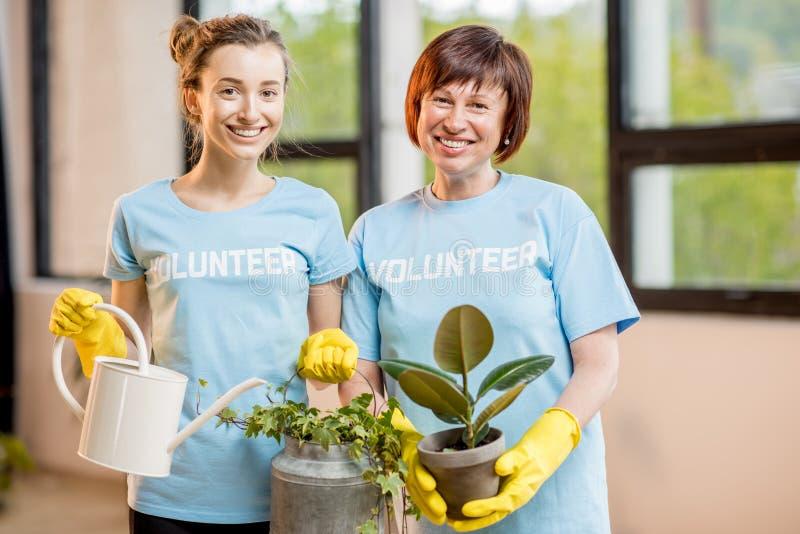 Voluntários que tomam das plantas fotografia de stock