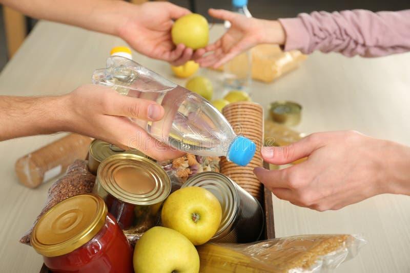 Voluntários que tomam o alimento fora da caixa da doação na tabela fotos de stock royalty free
