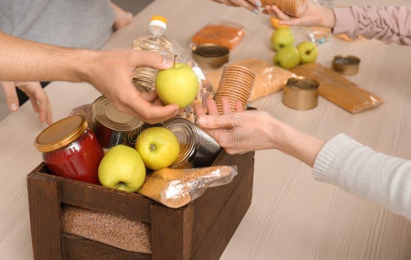 Voluntários que tomam o alimento fora da caixa da doação na tabela fotografia de stock