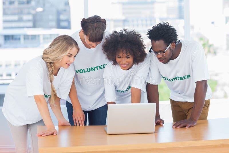 Voluntários que trabalham junto em um portátil imagens de stock