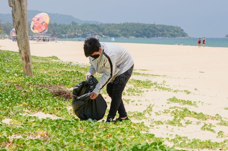 Volunt?rio da crian?a que recolhe o lixo na praia bonita na praia de Karon imagem de stock royalty free